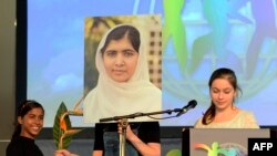 A girl holds a picture of Malala Yousafzai of Pakistan, winner of the 2014 World's Children's Prize for the Rights of the Child, during a press conference in Stockholm on October 28, 2014.