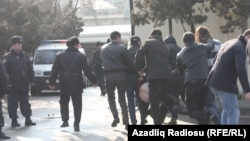 Police arrest two members of the band Bulistan at a youth opposition rally in Baku on March 17.