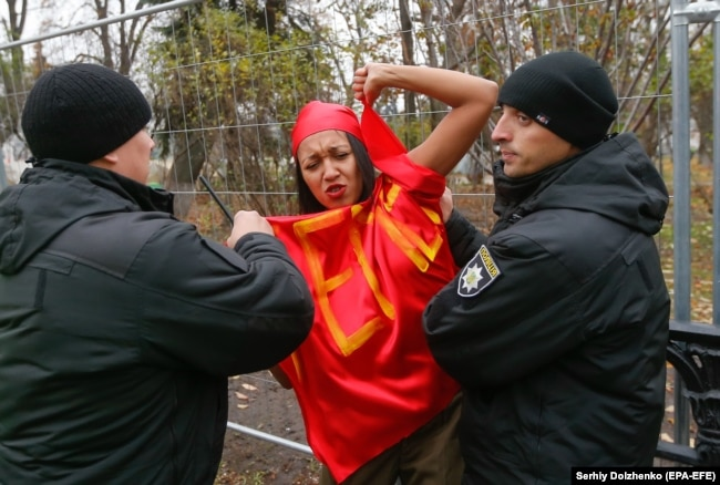 Ukrainian police detain a topless Femen activist during a protest in Kyiv in November 2017.