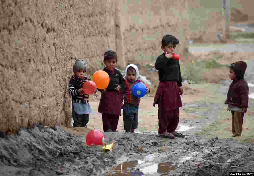 Afghan children play with balloons on a street in Kandahar Province. (AFP/Javed Tanveer)