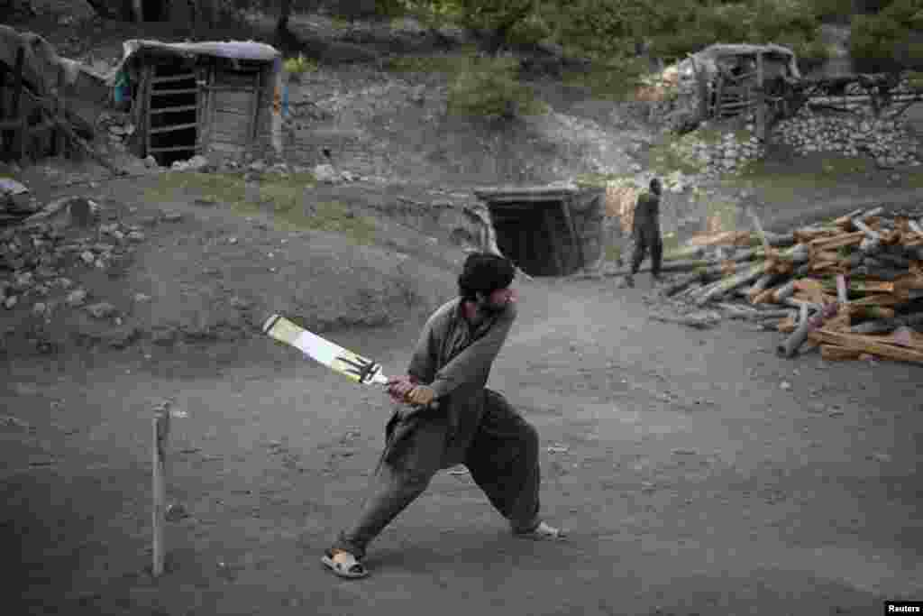 A miner plays cricket in the evening after the day's work is done.