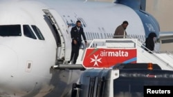 Passengers disembark from the hijacked Libyan flight on the runway at Malta airport.