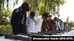 Former Taliban and IS militants surrender their weapons during a reconciliation ceremony in Jalalabad on August 28.