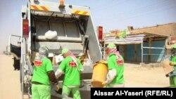عمال نظافة يجمعون القمامة في النجف