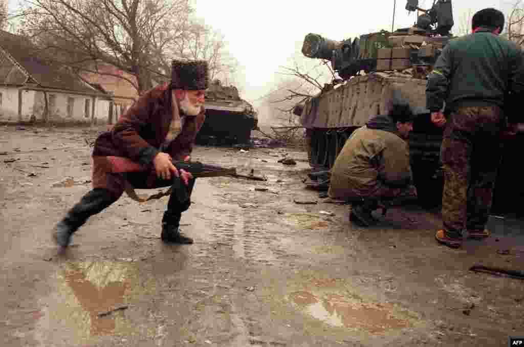 A Chechen volunteer takes cover behind a Russian tank during street fighting in Grozny. The first advances into the city were a disaster for ill-prepared Russian forces, who face a determined resistance.
