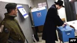 An Israeli border policeman stands guard as a man casts his ballot in Jerusalem for Israeli parliamentary elections.