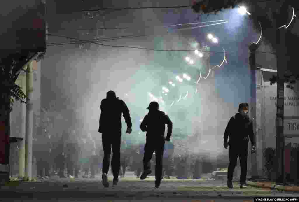 Protesters run away from tear gas during clashes with riot police in Bishkek.