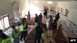 Pakistani security officials gather at a Shiite Muslim mosque after a bomb explosion in Shikarpur in the southern Sindh province on January 30.