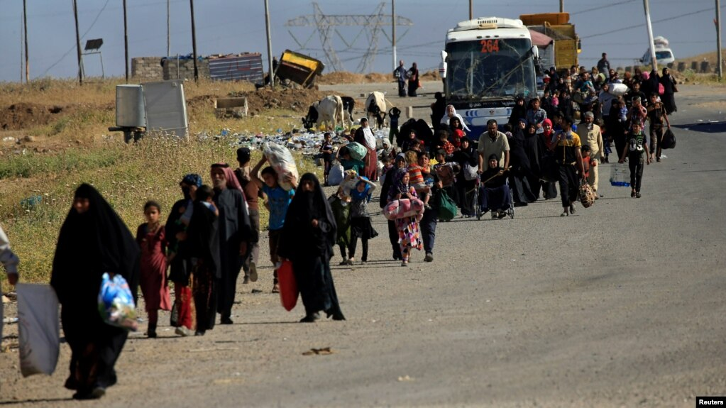 Displaced people flee fighting in Mosul.
