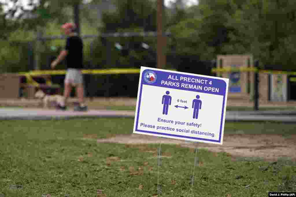 A sign is posted in a Houston park reminding people to practice social distancing. A stay-at-home order was issued on March 24 for Houston and Harris County residents to help fight the spread of COVID-19.