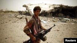 Një ushtar jemenas qëndron pranë një ndërtese të shkatërruar gjatë luftimeve me militantët islamik (Ilustrim)