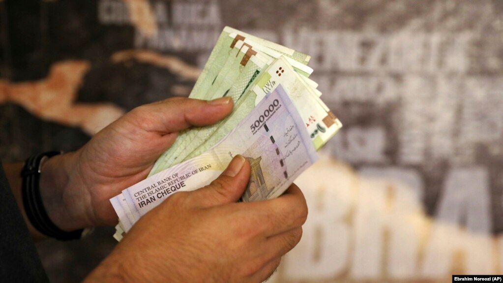 A man counts his banknotes and traveler's checks in Tehran, August 21, 2019