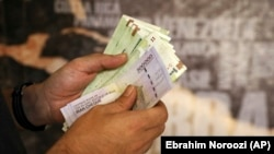 A man counts his banknotes and traveler checks in Tehran, August 21, 2019