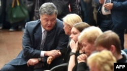 Ukrainian President Petro Poroshenko talks with relatives as he pays a tribute to Belarus-born journalist Pavel Sheremet, who was killed in a car bomb in central Kyiv on July 20.