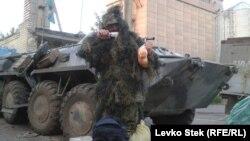 Солдат украинской армии позирует для фото с полученной посылкой.