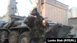 At Slovyansk's animal-feed factory, where a Ukrainian National Guard unit is stationed, one of the men poses dressed in a camouflage cloak he's just been delivered, holding a sausage and a bag of oranges.