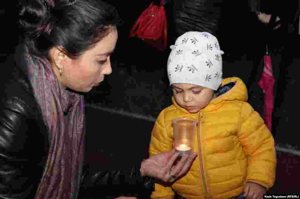 Ребенок заинтересовался одной из зажженных свеч в память о жертвах депортации.