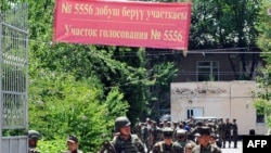 Soldiers leave after casting ballots during early voting at a polling station in Osh on June 25.