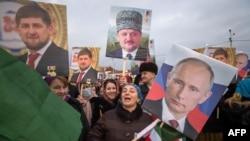 Люди на демонстранции держат портреты Владимира Путина, Рамзана Кадырова и его отца Ахмада Кадырова. Грозный, 22 января 2016 года.