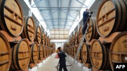 Moldova -- Employees fill a brandy barrel at the wine- and brandy distillery KVINT in Tiraspol, April 17, 2014