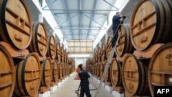 Работник молдавской фабрики по производству вина в хранилище.