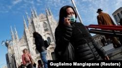 Прохожая в защитной маске в итальянском городе Милан.