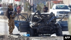 A soldier stands next to the site of a car-bomb attack in Kabul on November 13.