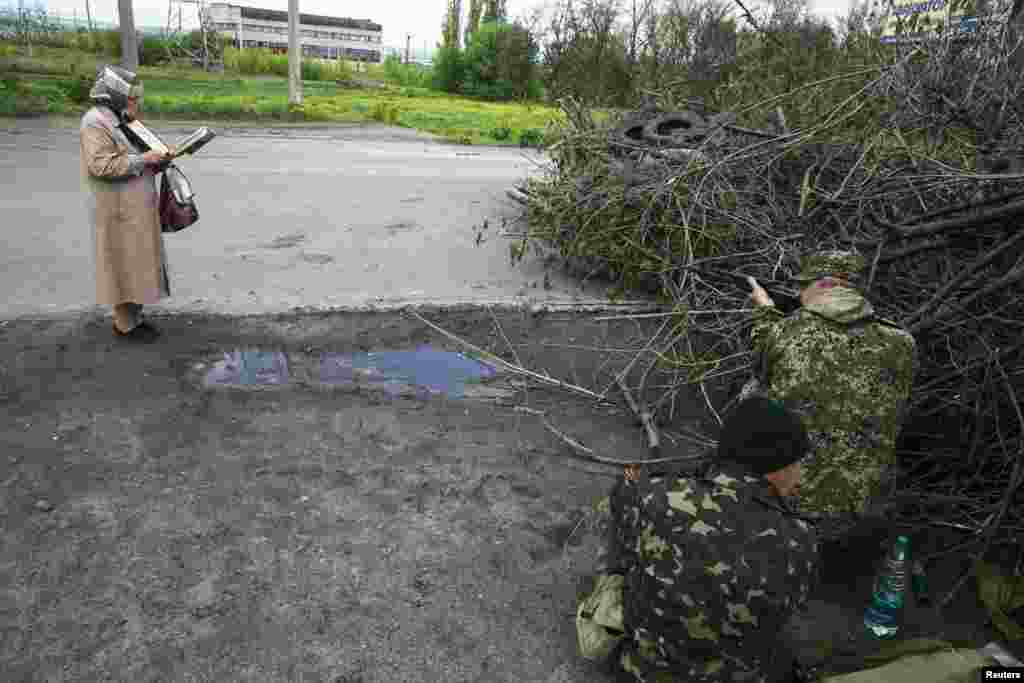 A woman reads the Bible as pro-Russia armed men take up positions near the eastern Ukrainian town of Slovyansk on May 5. (Reuters/Baz Ratner)