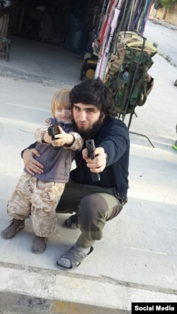 Mansur Shishani and a toddler posing with guns