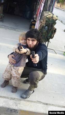 Mansur Shishani and a toddler posing with guns