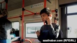 Мальчик с телефоном в салоне автобуса в Туркменистане.