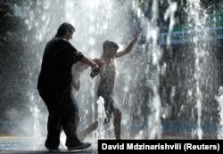 People cool off in a water fountain in Tbilisi.