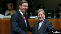 Serbian Prime Minister Aleksandar Vucic (left) posing with European Neighborhood Policy and Enlargement Negotiations Commissioner Johannes Hahn at the start of a European Union-Serbia accession conference in Brussels on December 14.
