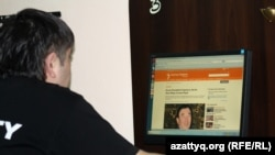 Молодой человек читает сайт Азаттык.