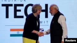 Britain's Prime Minister Theresa May shakes hands with her Indian counterpart Narendra Modi during the India-UK Tech Summit in New Delhi on November 7.
