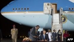 Президент США Барак Обама (в центре) расписывается в книге почетных гостей по прибытии в Кению. Найроби, 24 июля 2015 года.