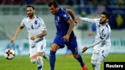 Two Kosovar players (in white) attempt to close down a Croatian forward during Kosovo's qualifying match for the 2018 World Cup last year.