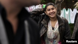 Leonarda Dibrani, 15, smiles as she walks in the town of Mitrovica on October 17, following her deportation from France.