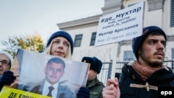 Activists hold a portrait and a placard with the names of Crimean Tatars, who are reportedly missing in Crimea, during a protest in front of the Russian Embassy in Kyiv last week.