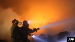 Палестинцы тушат пожар после израильских авиаударов