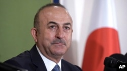Turkey's Foreign Minister Mevlut Cavusoglu attends a press conference Tuesday, Nov. 6, 2018, in Tokyo. Turkey's top diplomat has criticized the U.S. resumption of sanctions on Iran as unilateral, not wise and dangerous, calling for a dialogue and compromi