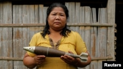 Жена държи бомба от войната във Виетнам, амерена в Лаос през 2016 г.