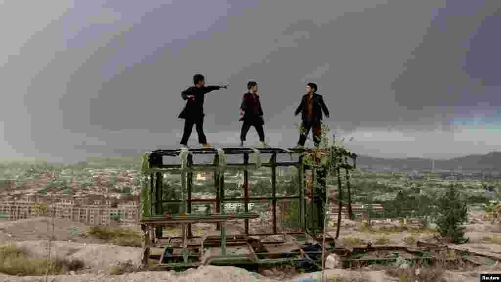 Afghan boys play on a destroyed car on a hilltop in Kabul, Afghanistan, on October 18. (REUTERS/Mohammad Ismail)