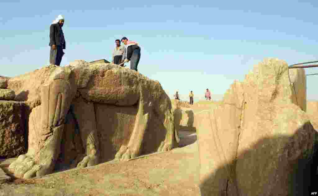 Photographs taken in July 2001 (above and below) show Iraqi workers cleaning a statue of a winged bull and attending to other areas of an archaeological site in Nimrud.