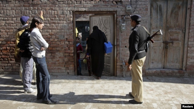 A policeman stands guard as female polio workers wait to administer polio vaccines to children in Lahore, Pakistan, on December 20.