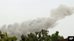 A smoke plume rises over Tripoli early on June 7, which correspondents say appeared to be in the vicinity of Muammar Qaddafi's residential compound.