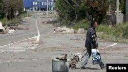 Мужчина с тележкой на улице возле разрушенного супермаркета Metro Cash&Carry. Донецк, июль 2015 года