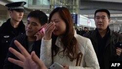 Жоғалған ұшақты қарсы алмақ болған әйел жылап тұр. Пекин, 8 наурыз 2014 жыл.