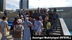 Многодетные матери, пытающиеся пройти к резиденции президента Казахстана, путь к которой преградили сотрудники спецподразделения полиции. Нур-Султан, 12 июля 2019 года.