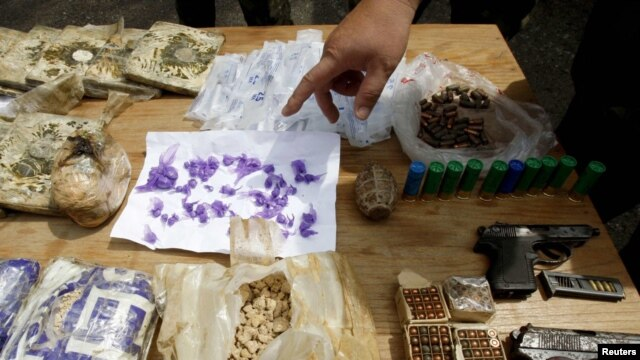 Kyrgyz policemen inspect drugs and weapons, suspected to have been used during ethnic clashes, seized in raids in the city of Osh. (file photo)
